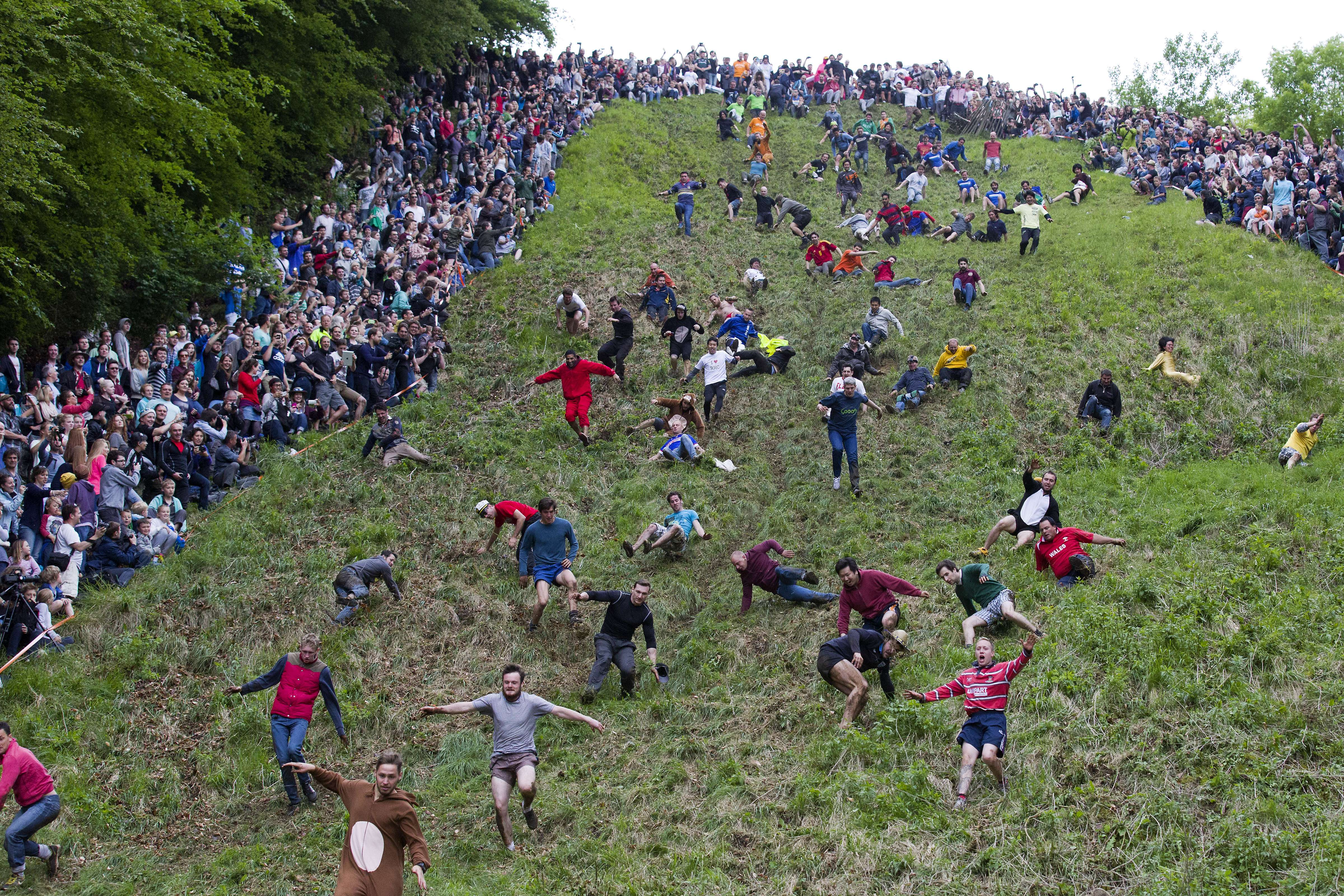 Competitors tumble down Coopers Hill in pursuit of a round Double Gloucester cheese during the annual cheese rolling and wake near the village of Brockworth near Gloucester in western England on May 26, 2014. With a disputed history dating back to at least the 1800s, the annual Cooper's Hill Cheese Rolling involves hordes of fearless competitors chasing an eight pound Double Gloucester cheese down a steep hill. The slope has a gradient in places of 1-in-2 and in others 1-in-1, its surface is very rough and uneven and it is almost impossible to remain on foot for the descent. The winner of the race down the hill wins the cheese.AFP PHOTO / JUSTIN TALLISJUSTIN TALLIS/AFP/Getty Images ORG XMIT: 1095